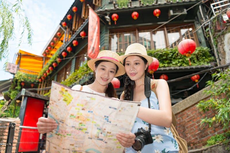 Turista asiático de duas mulheres que olha no mapa foto de stock