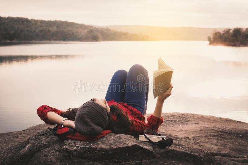 Turista asiático de relaxamento do momento que lê um livro na rocha fotografia de stock royalty free