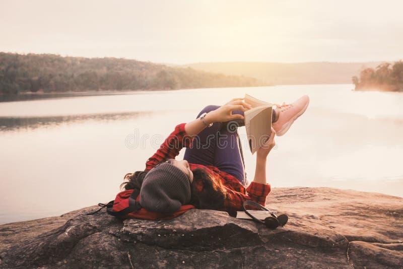Turista asiático de relaxamento do momento que lê um livro na rocha imagens de stock royalty free