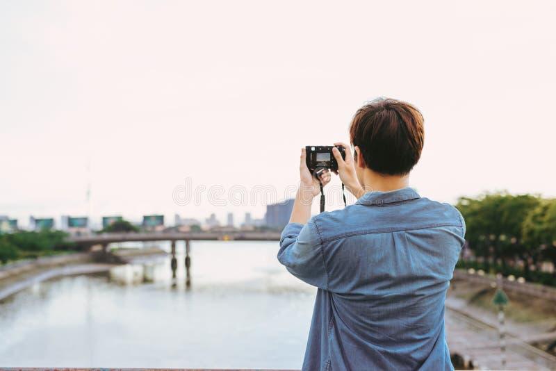 Turista asiático novo do homem que toma as fotos exteriores na cidade foto de stock