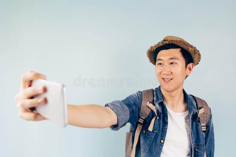 Turista asiático novo que sorri e que toma um selfie isolado sobre o fundo azul pastel fotografia de stock royalty free