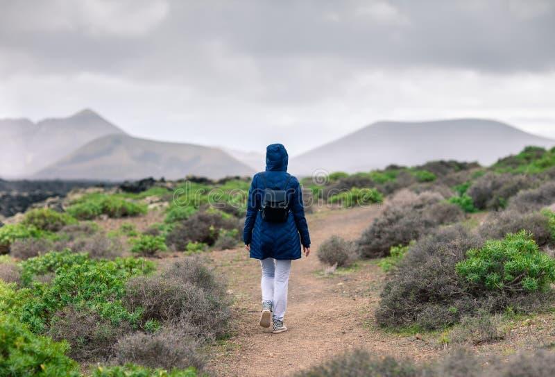 Turista attivo della donna che cammina sulla strada alle montagne immagine stock