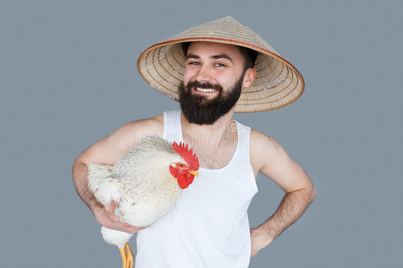 Turista barbudo de Tailandia del hombre que presenta con el gallo blanco del pollo foto de archivo libre de regalías