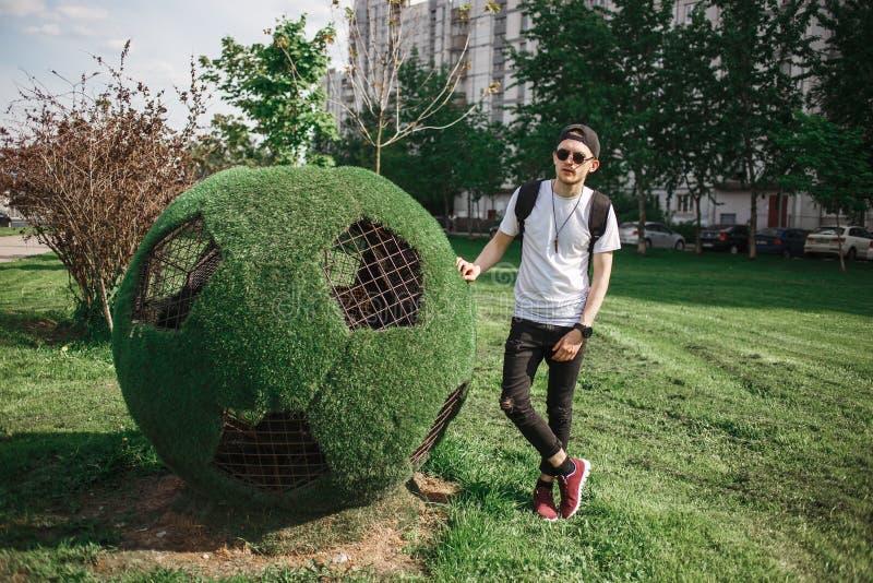 Turista bello alla moda dell'uomo che posa vicino al simbolo del pallone da calcio di erba Concetto russo della coppa del Mondo fotografia stock