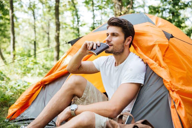 Turista bello dell'uomo che si siede e che beve dalla boccetta in foresta immagini stock