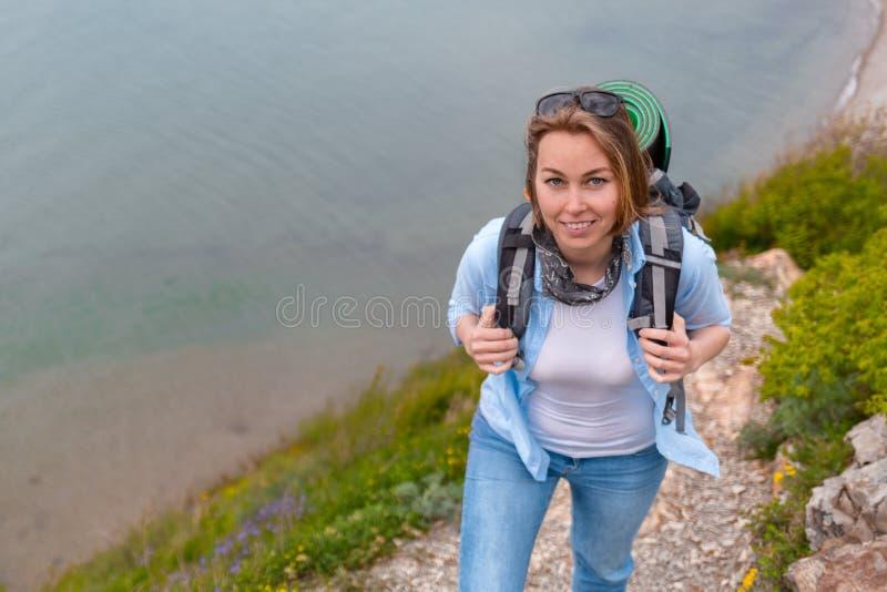 Turista bonito da mulher que anda ao longo de uma fuga de montanha Caminhada e esportes Fim acima imagem de stock