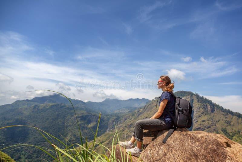 Turista bonito novo feliz da menina com uma trouxa Sente-se nas montanhas e aprecie-se a vista e a natureza imagem de stock royalty free