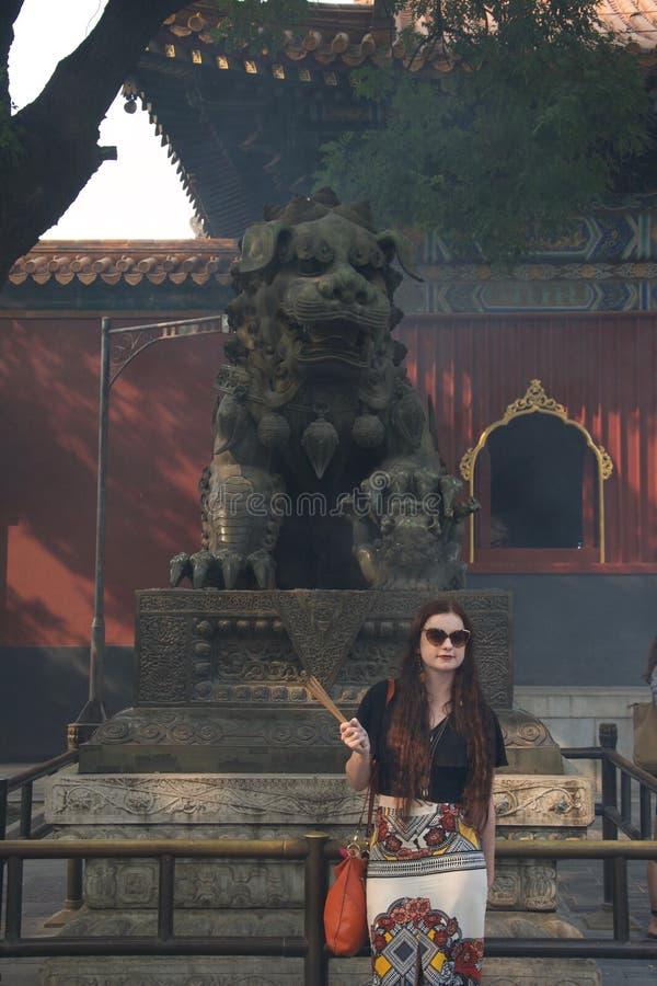 Turista caucásico femenino de moda con incienso en templo chino delante del estatuto fotografía de archivo libre de regalías