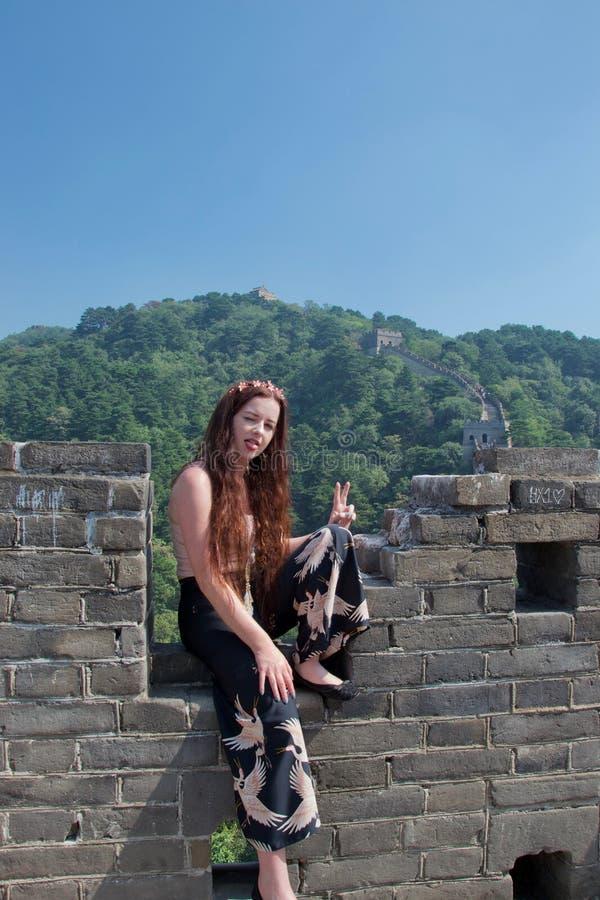 Turista caucasiano f?mea elegante que levanta no Grande Muralha de China foto de stock