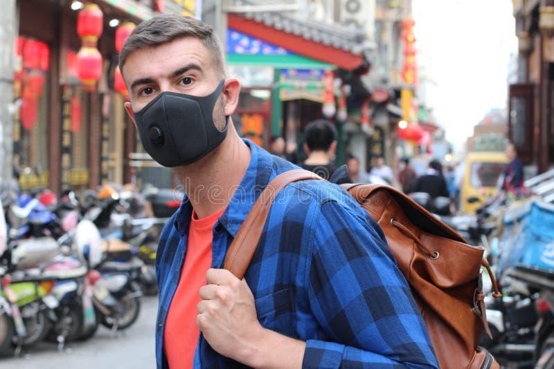 Turista caucasico che utilizza la maschera di inquinamento in Asia immagini stock