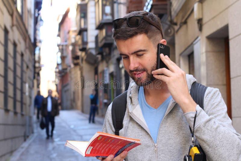 Turista che chiama dal telefono mentre esaminando la guida o il dizionario di turismo immagini stock
