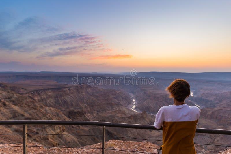 Turista che esamina il canyon del fiume del pesce, destinazione scenica di viaggio in Namibia del sud Vista ultra grandangolare d fotografia stock