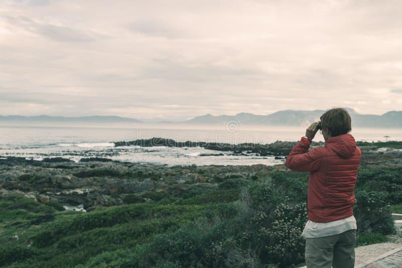 Turista che guarda con binoculare sulla linea rocciosa della costa De Kelders, Sudafrica, famoso per la sorveglianza della balena fotografia stock libera da diritti