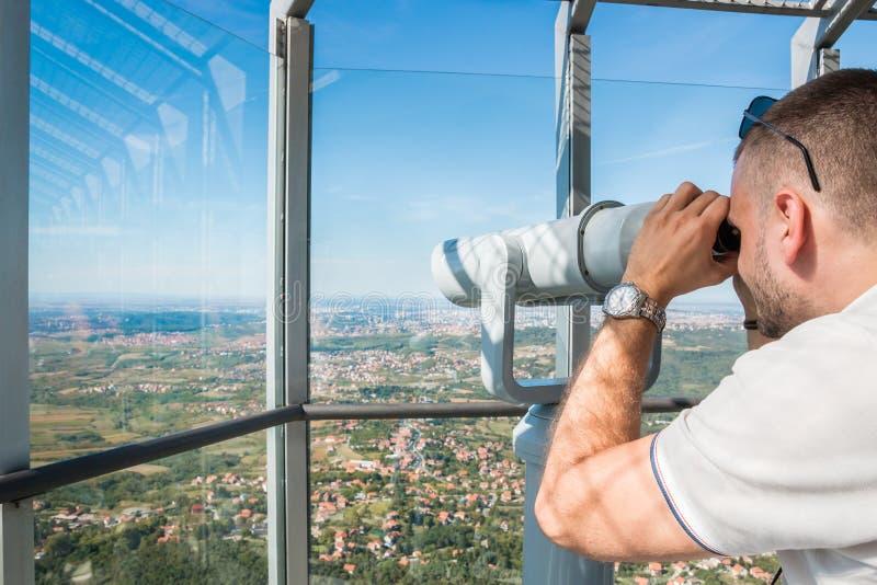 Turista che osserva tramite il telescopio immagine stock