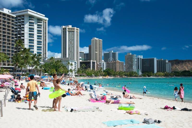 Turista che prende il sole e che pratica il surfing sulla spiaggia di Waikiki in Hawai. fotografia stock libera da diritti