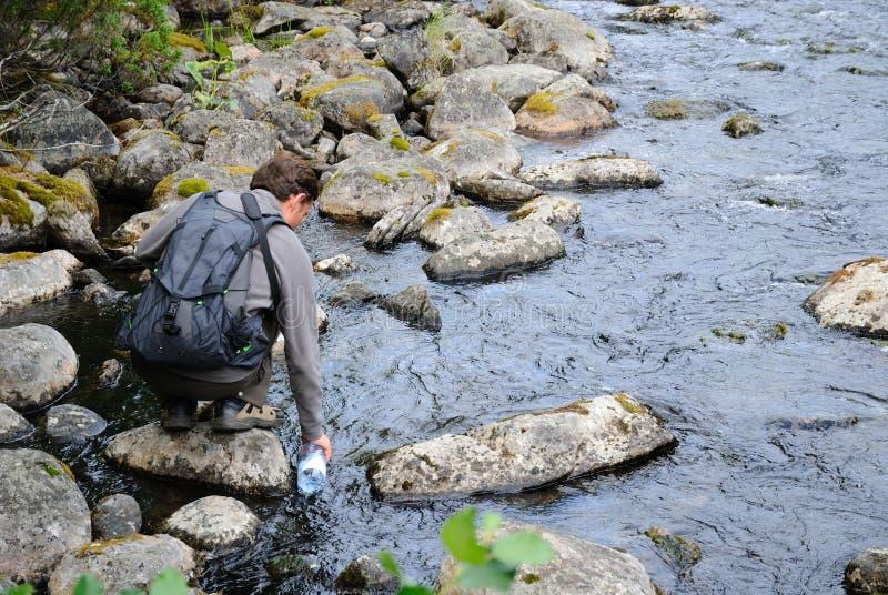Turista che riempie la bottiglia di acqua dal fiume. fotografie stock