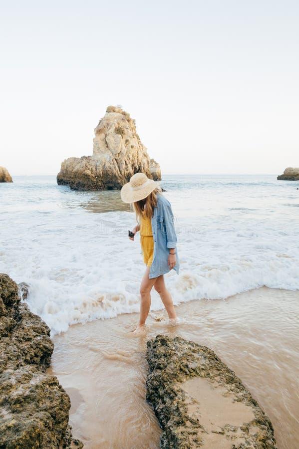 Turista che sembra modello femminile che cammina sulla spiaggia Barranco das Canas vicino a Portimao, Portogallo fotografia stock