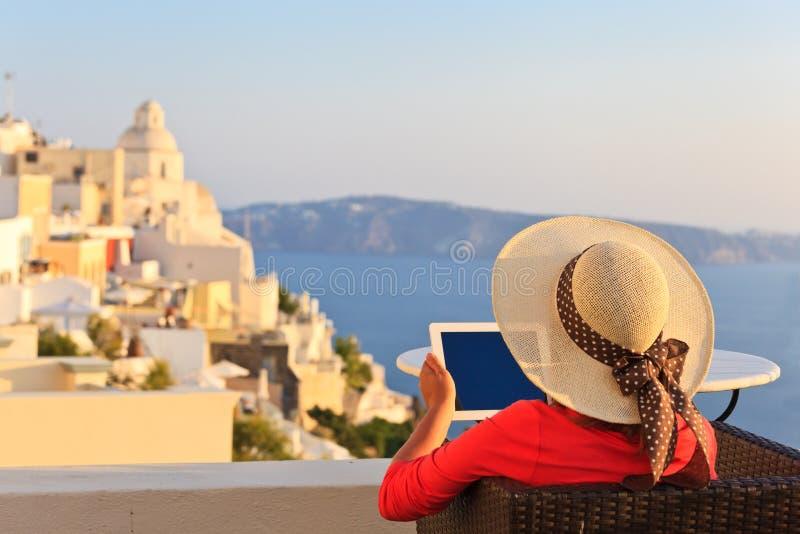 Turista com a almofada de toque em Santorini fotografia de stock