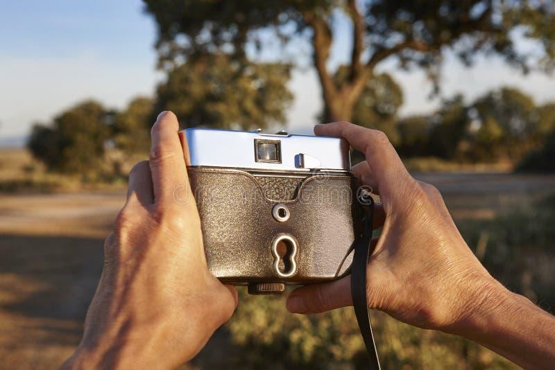 Turista com a câmera do vintage no campo Backgroun do curso foto de stock royalty free