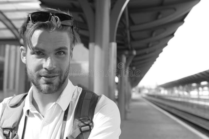 Turista com cara e a trouxa de sorriso, espaço da cópia Trem faltado e conceito de viagem Homem novo que está na plataforma fotos de stock royalty free