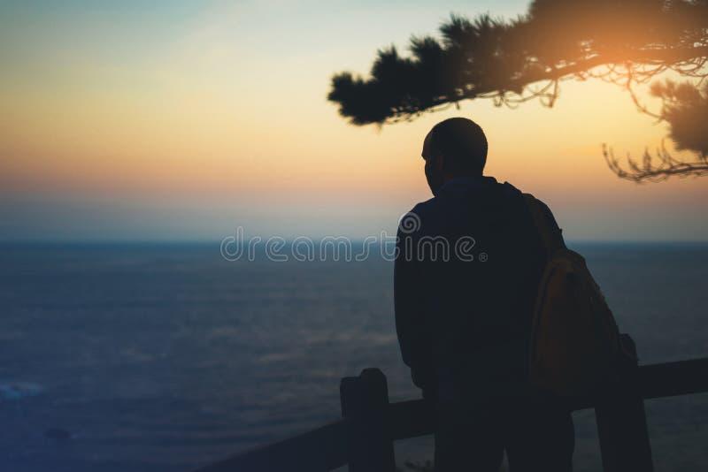 Turista com vista da trouxa de por do sol surpreendente do seascape no mar azul do fundo, indivíduo do caminhante do moderno que  imagem de stock