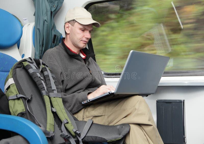 Turista con la computadora portátil en el tren fotos de archivo