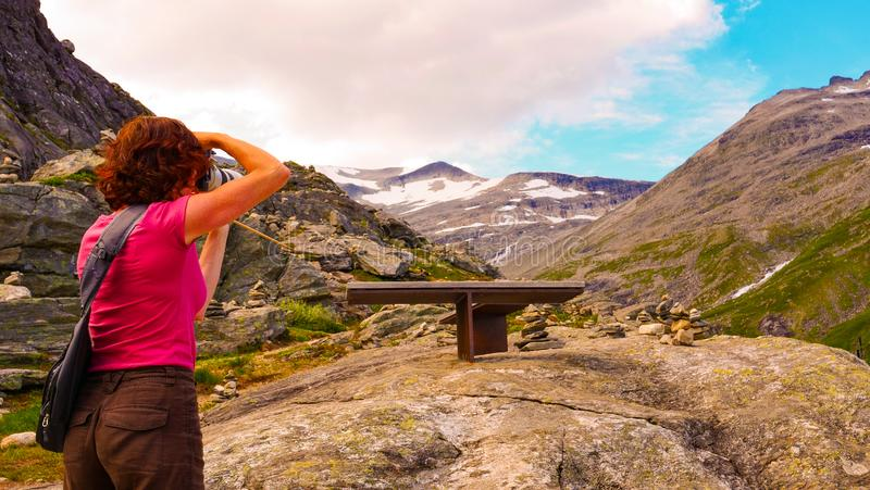 Turista con la macchina fotografica sul punto di vista di Trollstigen fotografie stock libere da diritti