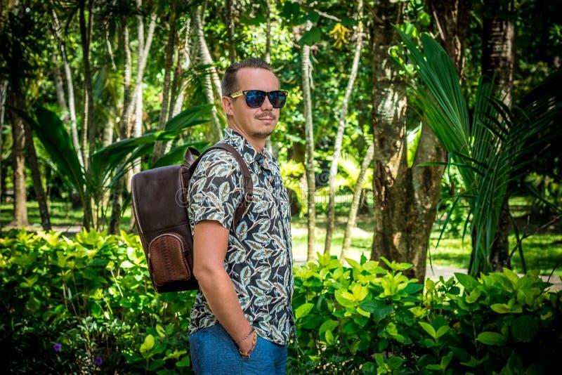 Turista con la mochila marrón elegante del pitón del snakeskin en el parque asiático Bali, Indonesia Hombre caucásico hermoso ade foto de archivo libre de regalías