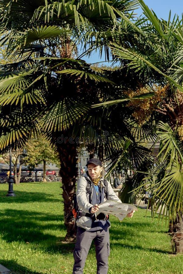 Turista con un mapa en el fondo de palmas imagen de archivo