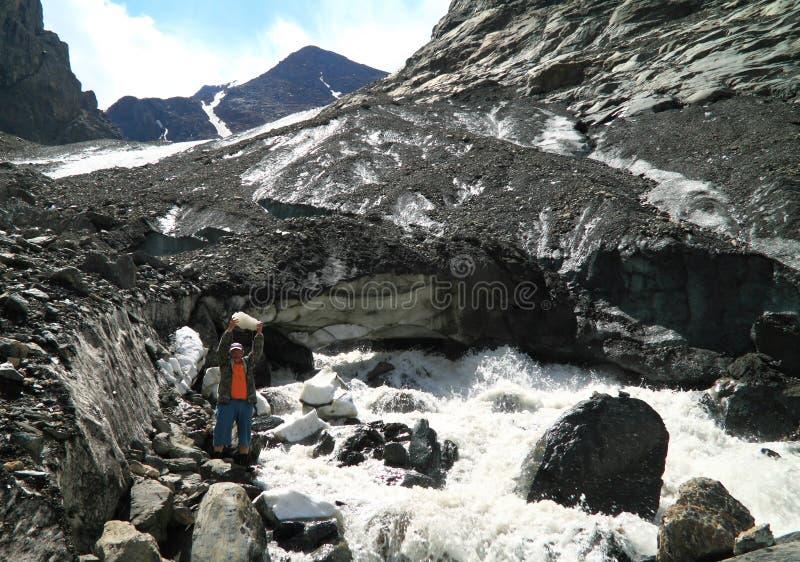 Turista con un pedazo de un hielo en un fondo de un glaciar del deshielo en las montañas de Altai foto de archivo libre de regalías