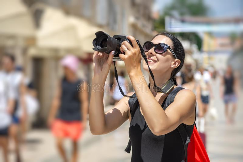 Turista con una macchina fotografica che fotografa le vie un giorno soleggiato immagine stock libera da diritti