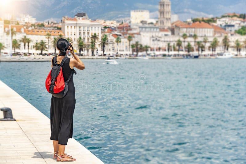 Turista con una macchina fotografica che fotografa le vie un giorno soleggiato fotografia stock libera da diritti
