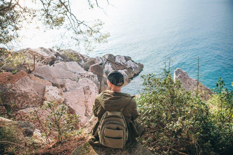 Turista con una mochila cerca del mar imagenes de archivo