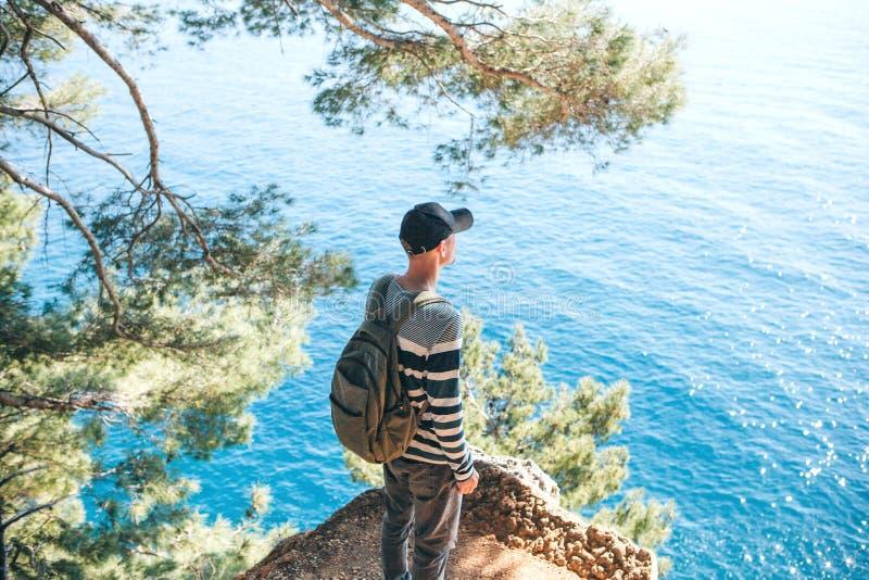 Turista con una mochila cerca del mar fotos de archivo