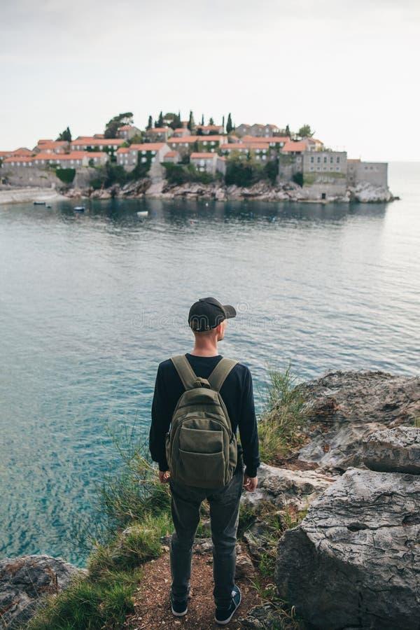 Turista con una mochila cerca del mar imágenes de archivo libres de regalías