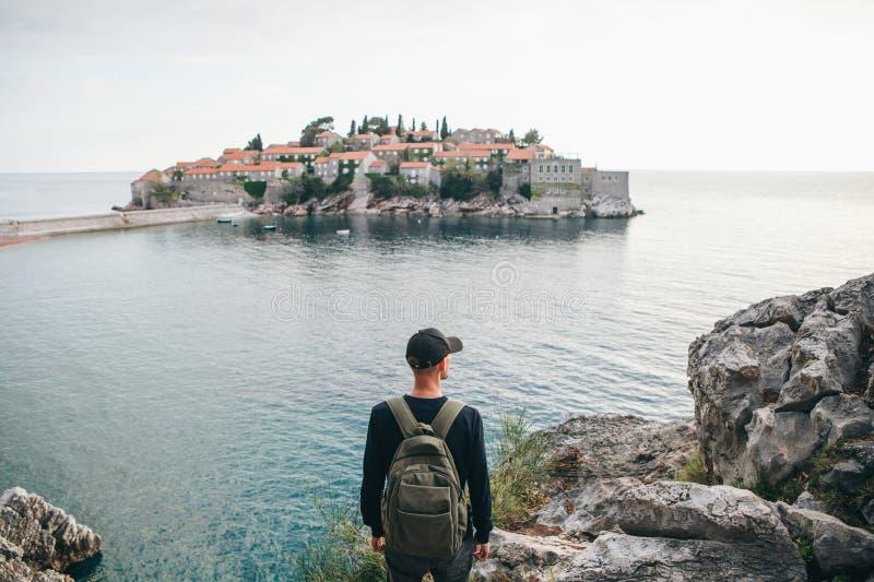 Turista con una mochila cerca del mar foto de archivo