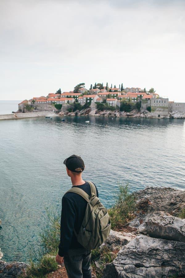 Turista con una mochila cerca del mar fotografía de archivo