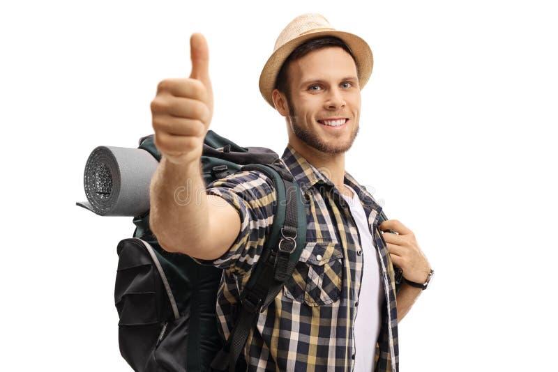 Turista con una mochila que hace un pulgar encima de la muestra fotografía de archivo