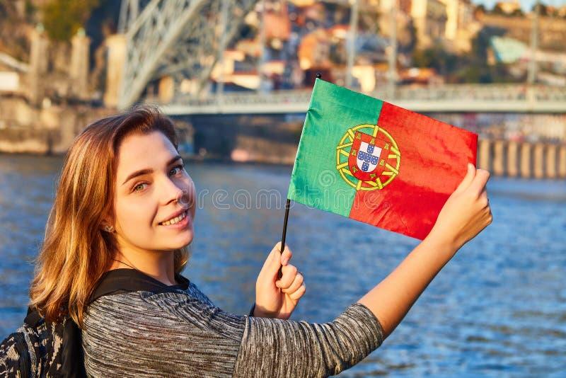 Turista da jovem mulher com bandeira portuguesa que aprecia a opinião bonita da paisagem na cidade velha com rio e os DOM famosos imagem de stock royalty free