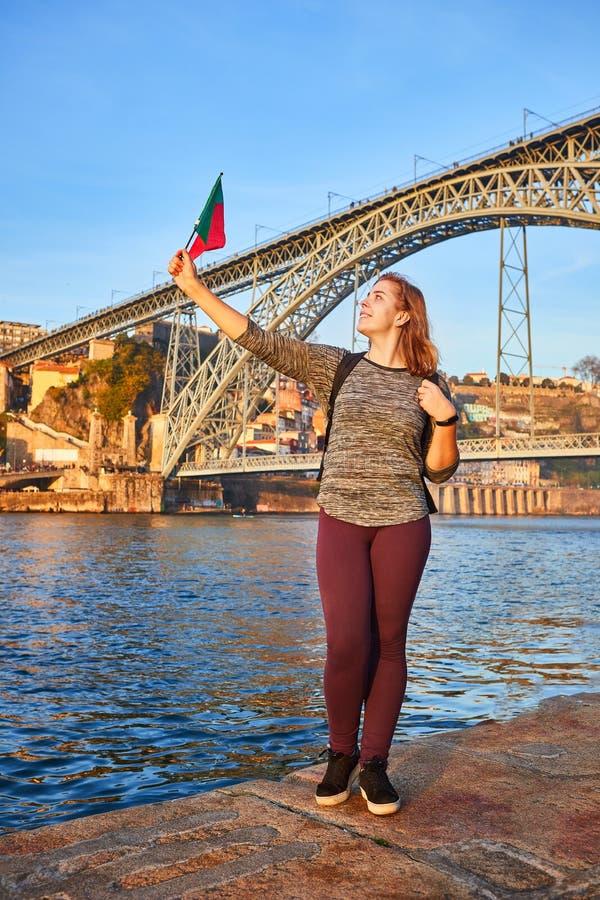 Turista da jovem mulher com bandeira portuguesa que aprecia a opinião bonita da paisagem na cidade velha com rio e os DOM famosos fotografia de stock