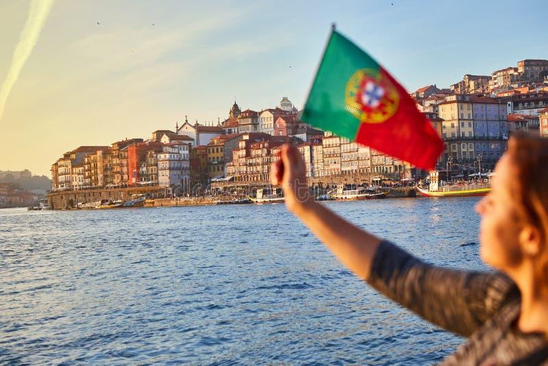 Turista da jovem mulher com bandeira portuguesa que aprecia a opinião bonita da paisagem no quarto e no rio históricos de Ribeira foto de stock royalty free