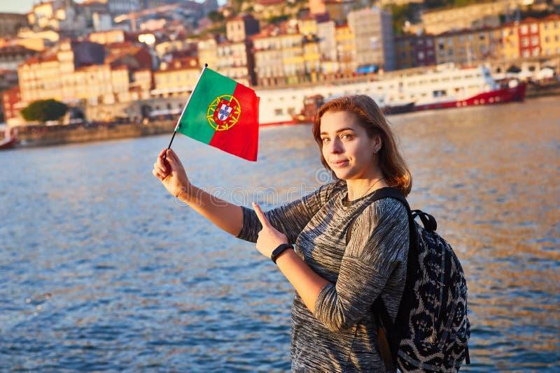 Turista da jovem mulher com bandeira portuguesa que aprecia a opinião bonita da paisagem no quarto e no rio históricos de Ribeira fotos de stock