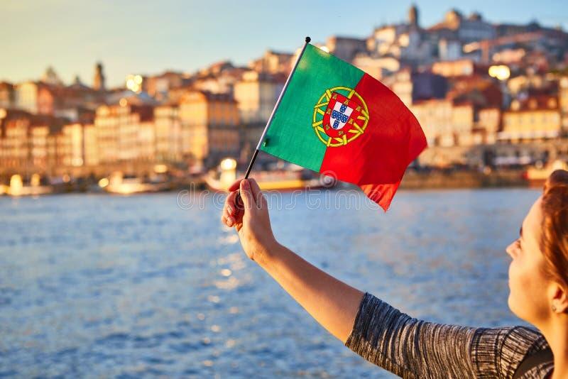 Turista da jovem mulher com bandeira portuguesa que aprecia a opinião bonita da paisagem no quarto e no rio históricos de Ribeira fotografia de stock