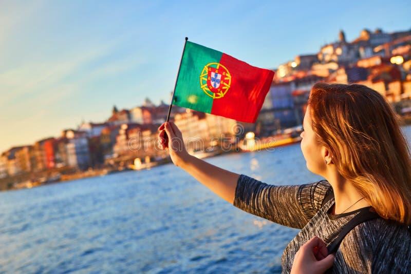 Turista da jovem mulher com bandeira portuguesa que aprecia a opinião bonita da paisagem no quarto e no rio históricos de Ribeira imagem de stock royalty free