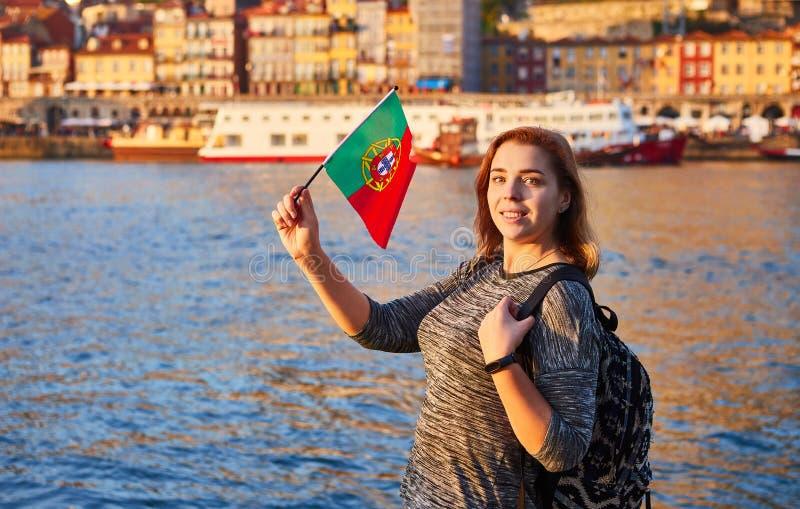 Turista da jovem mulher com bandeira portuguesa que aprecia a opinião bonita da paisagem no quarto e no rio históricos de Ribeira imagem de stock