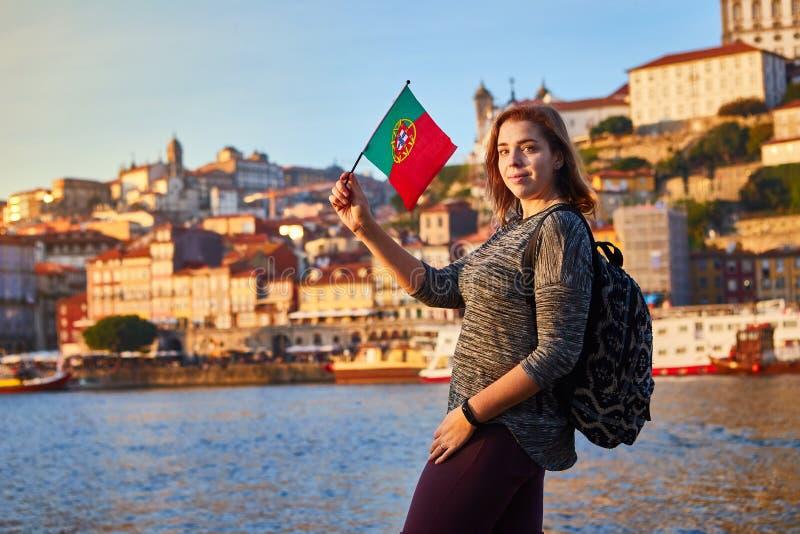 Turista da jovem mulher com bandeira portuguesa que aprecia a opinião bonita da paisagem no quarto e no rio históricos de Ribeira foto de stock