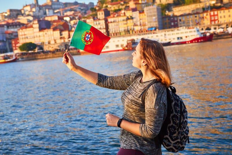 Turista da jovem mulher com bandeira portuguesa que aprecia a opinião bonita da paisagem no quarto e no rio históricos de Ribeira fotos de stock royalty free