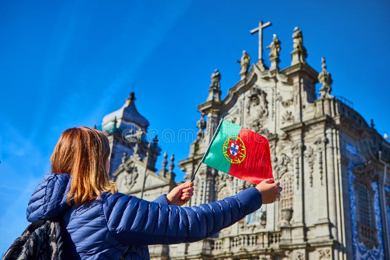 Turista da jovem mulher com posição portuguesa da bandeira perto da igreja de Congregados Carmelites com as telhas azuis portugue fotografia de stock royalty free