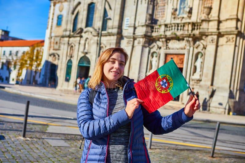 Turista da jovem mulher com posição portuguesa da bandeira perto da igreja de Congregados Carmelites com as telhas azuis portugue imagem de stock royalty free