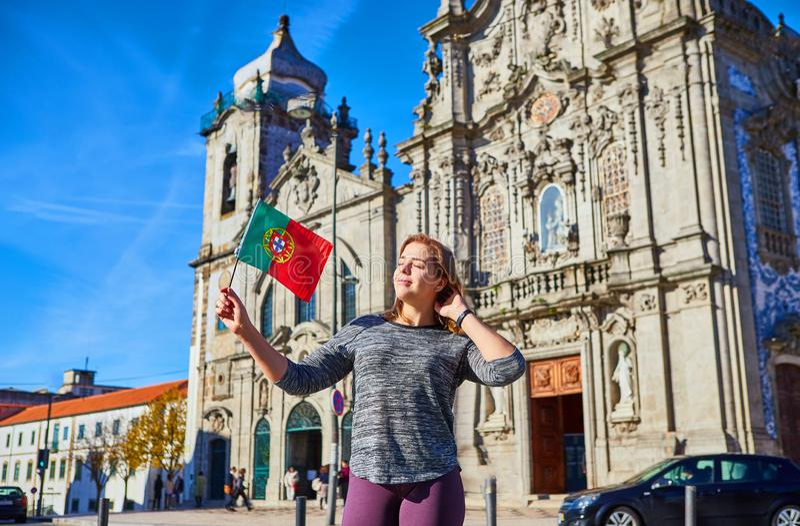 Turista da jovem mulher com posição portuguesa da bandeira perto da igreja de Congregados Carmelites com as telhas azuis portugue imagens de stock